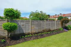 Neat flower bed with garden fence and lawn. Royalty Free Stock Photography