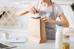 Neat hostess unpacking after shopping. What do we got there. Nice careful young lady taking food products out of the paper bag and sorting them out while Royalty Free Stock Photos