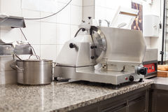 Neat interior of a commercial kitchen. With wall mounted utensils and a range of different stainless steel pots arranged on a central gas hob Royalty Free Stock Photography