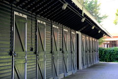 Neat line of stall doors in long green stable Royalty Free Stock Photo