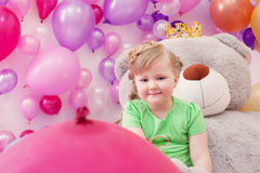 Neat little girl posing in studio with balloons Stock Photography