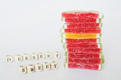 A neat stack of marmalade lies on a white surface. Nearby are the words composed of letters: sugar and dessert. Sweets royalty free stock photography