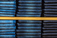 Neat stacks of folded jeans. On the shop shelves Stock Image