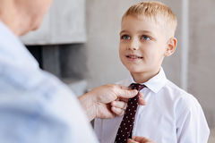 Neat stylish grandpa helping his grandson with a tie Royalty Free Stock Photography
