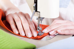 Neat tailor sewing a fabric. Neat tailor sewing orange fabric very precisely Stock Photo
