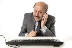 Neat and tidy 60s mature senior business man using mobile phone. At office desk working happy and gesturing funny  on white background in communication concept Royalty Free Stock Photo
