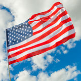 Neat USA flag with cumulus clouds on background - outdoors shot Royalty Free Stock Photography