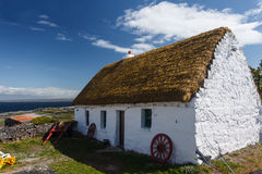 A neat whitewashed Irish cottage on the island of Inishee. A neat whitewashed thatched roof Irish cottage on the island of Inishee  with wagon wheels and farm Royalty Free Stock Photography