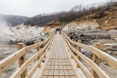 Neat wooden walk way at Noboribetsu Jigokudani Hell Valley: The volcano valley got its name from the sulfuric smell. Neat wooden walk way at Noboribetsu stock photo