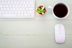 Neat workstation on a wooden desk. Viewed from overhead with a wireless computer mouse and keyboard, cup of coffee and houseplant Stock Photos