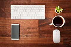 Neat workstation on a wooden desk. Viewed from overhead with a wireless computer mouse and keyboard, mobile phone, cup of coffee and houseplant Stock Photo