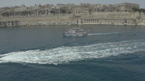 Drone neatly circled around the boats, on background sees Valletta, Malta. Old, city. - 4K stock video