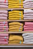 Neatly folded clothes. Rack of clothes with warm. Wooden cabinet with a stack of sweaters. Coloured clothing. Neat stacks of. Folded clothing on the shop stock images