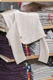 Neatly folded clothes. Rack of clothes with warm. Wooden cabinet with a stack of sweaters. Coloured clothing. Neat stacks of. Folded clothing on the shop royalty free stock image