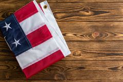 Neatly folded patriotic American Flag on wood. Neatly folded patriotic American Flag showing the stars and stripes on a rustic wood table with copy space for stock images