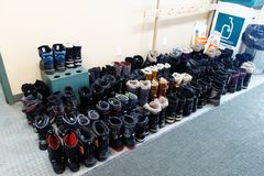 Neatly lined up winter boots. Sixty five pairs of winter boots neatly lined up in a Quebec cross country ski station stock photo