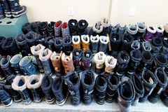 Neatly lined up winter boots. Sixty five pairs of winter boots neatly lined up in a Quebec cross country ski station royalty free stock image