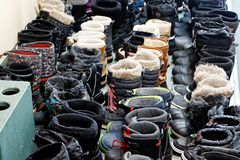 Neatly lined up winter boots. Sixty five pairs of winter boots neatly lined up in a Quebec cross country ski station royalty free stock photography