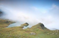Nebbia bassa sopra il lago alpino nella mattina Immagini Stock