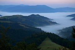 Nebbia di mattina nelle montagne dei Carpathians fotografia stock