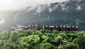 Nebbia di mattina sopra i cottage di legno nelle montagne Fotografia Stock Libera da Diritti
