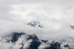 Nebbia intensa e nuvole che riguardano il picco di una montagna sulle Ande Immagini Stock