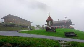 nebbia l'austria ` Alpino di Stubai del ` di regione Parcheggio, ristorante, ` di Oberris del ` di cappella nel ` di Oberbergtal  fotografie stock