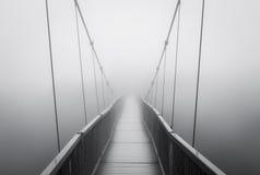 Nebbia pesante spettrale sul ponte sospeso che sparisce nello sconosciuto terrificante Immagine Stock Libera da Diritti
