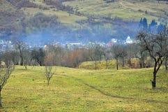 Nebbia sopra il villaggio della valle Immagine Stock