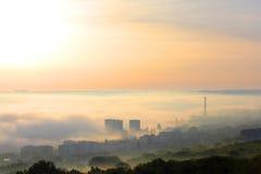 Nebbia sopra la città all'alba Immagini Stock