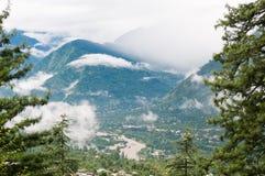 Nebbia in una valle fra le alte montagne Immagine Stock