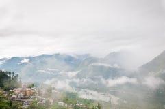 Nebbia in una valle fra le alte montagne Fotografia Stock