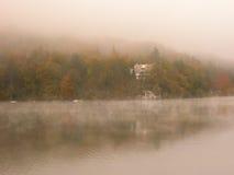 Nebel über dem See mit bunten Bäumen und Haus. Lizenzfreie Stockbilder