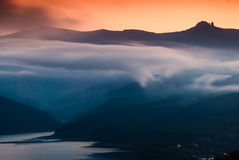 Nebel über hohem Berg und See Stockbild