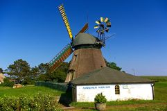Nebel, Amrum, Germany - June 1st, 2016 - Historic thatched-roof windmill with bright yellow sails and small whitewashed museum bui Royalty Free Stock Photos