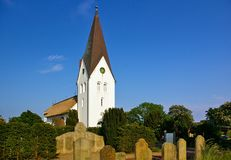 Nebel, Amrum, Germany - June 1st, 2016 - Historic whitewashed church in front of a blue sky with graveyard and ancient headstones Royalty Free Stock Image