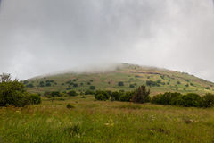 Nebel auf grünem Berg lizenzfreie stockfotografie