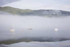 Nebel auf Wasser mit drei Booten Stockbild