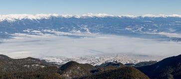 Nebel bedeckt die Stadt am Fuß der Berge Stockfotos