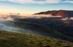 Nebel, der über den Hügeln bei Sonnenaufgang rollt Stockbild
