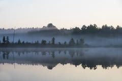 Nebel des frühen Morgens auf einem ruhigen See Stockfotos