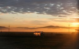 Nebel im Tal und in einem Gewächshaus wird durch die Sonne über den Bergen belichtet lizenzfreies stockbild