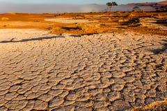 Nebel kontrastiert zu getrockneter gebrochener Flussbettschlammoberfläche Namibier-Wüste Stockbild