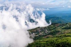 Nebel und Dorf auf Berg Lizenzfreies Stockfoto
