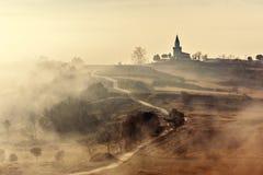 Nebelhafte Landlandschaft mit Kirche Lizenzfreies Stockfoto