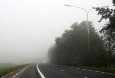 Nebelhafte Straße mit den Autoscheinwerfern weit entfernt Stockbilder