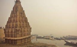 Nebelhafte Szene von der Ganges-Riverbank und von heiligem überschwemmtem Shiva-Tempel in Varanasi Stockfotografie