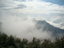 Nebelhafter Berg mit den Wolken, die auf sehr niedriger Höhe sich bewegen Lizenzfreie Stockfotos