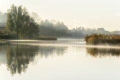 Nebelhafter Herbstmorgen mit Reflexionen im Wasser Lizenzfreie Stockbilder