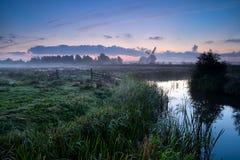 Nebelhafter Morgen über niederländischem Ackerland mit Windmühle und Fluss Stockbild
